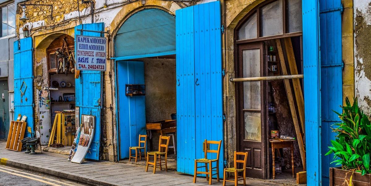 Tienda tipica con portalones azules abiertos y sillas en la acera en Larnaca, Chipre