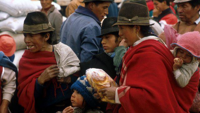 Mujeres con niños comprando en un mercado de Ecuador