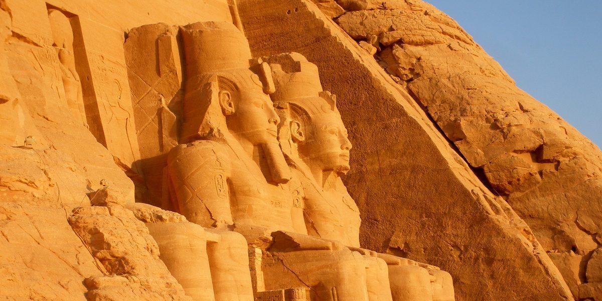 Esculturas en la fachada de uno de los templos de Abu Simbel iluminados por la luz del sol al amanecer, en Egipto