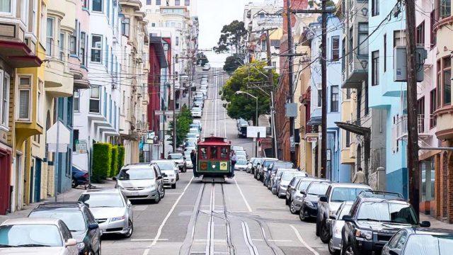 Calle en cuesta de SanFrancisco con tranvía y casas multicolores, en Estados Unidos
