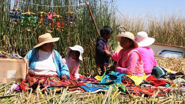 Mujeres en la isla de los Uros, Puno y Titicaca, sentadas en el suelo y al sol trabajando en diferentes tejidos y bordados, en Perú